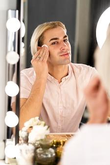 Homem usando almofadas de algodão para limpar a pele do rosto
