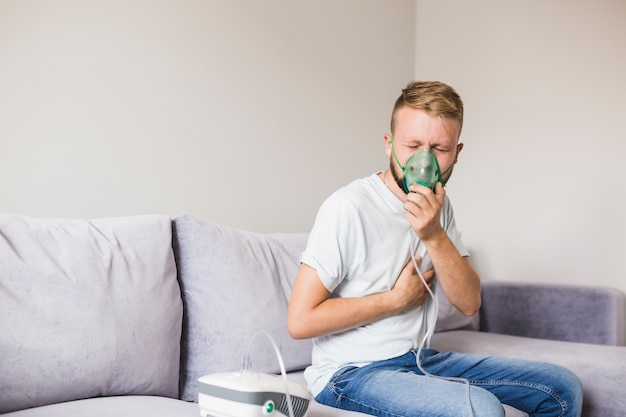 Homem, usando, asma, nebulizer, segurando mão, ligado, peito