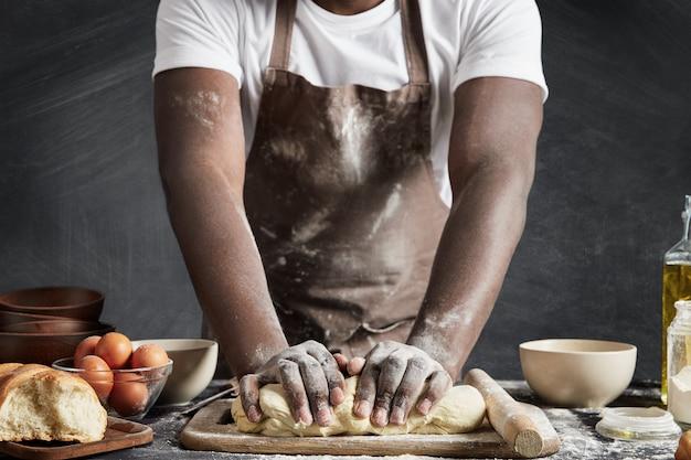 Homem usando avental assando na cozinha