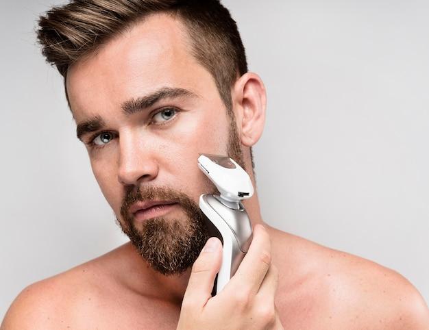 Homem usando barbeador elétrico