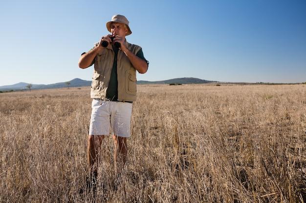 Homem, usando, binocular, ligado, paisagem