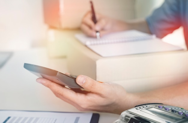 Homem usando calculadora e calcular para sua pequena empresa em casa.