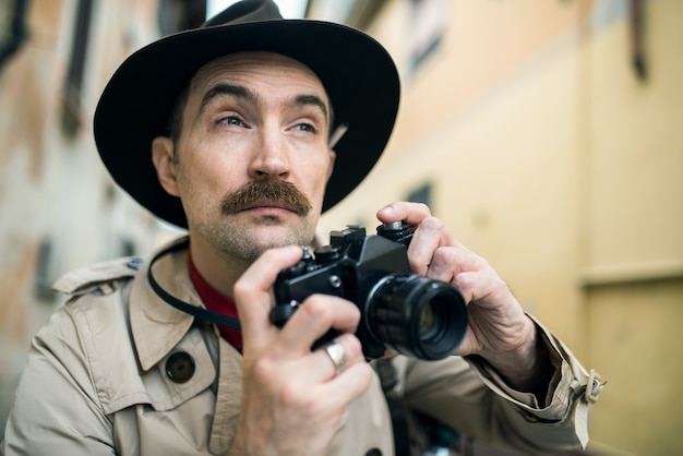 Homem usando câmera vintage em uma rua da cidade