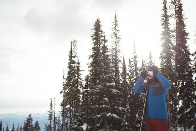 Homem usando capacete contra árvores