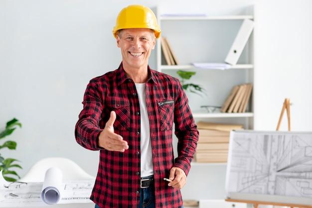 Homem usando capacete de segurança e dando um aperto de mão