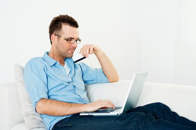 Homem usando cartão de crédito e laptop no sofá