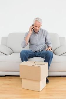 Homem usando cellpone em sofá com caixas em casa