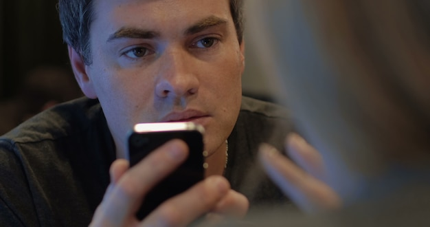 Homem usando celular e falando com mulher