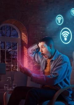 Homem usando celular e recebendo notificações de neon em casa à noite sentado na poltrona assistindo