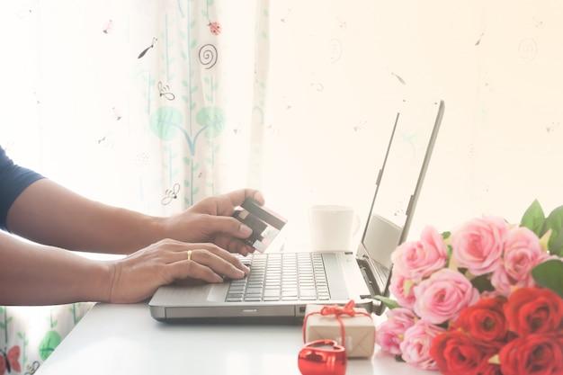 Homem, usando computador, e, cartão crédito, com, presente, e, rosas, ligado, tabela