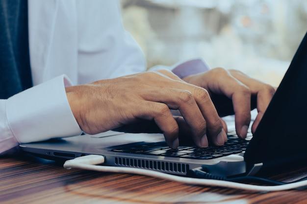 Homem usando computador, negociando online em casa