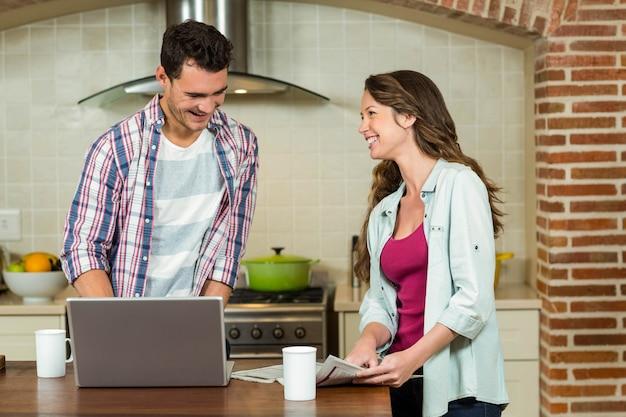 Homem, usando computador portátil, e, mulher, jornal leitura, ligado, cozinha, worktop