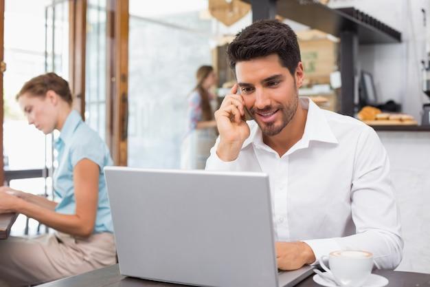 Homem, usando computador portátil, e, telefone móvel, em, loja café