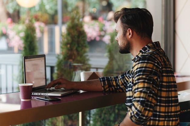 Homem, usando computador portátil, em, loja café