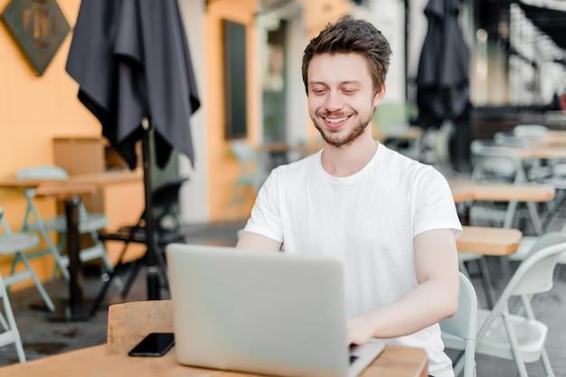 Homem, usando computador portátil, para, trabalho remoto, em, café