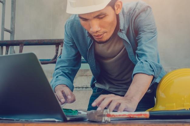 Homem usando computador, trabalhando em construção com capacete rígido