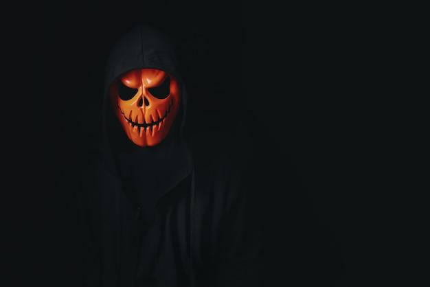 Homem usando cosplay assustador de caveira de abóbora vestido de preto para o festival de halloween