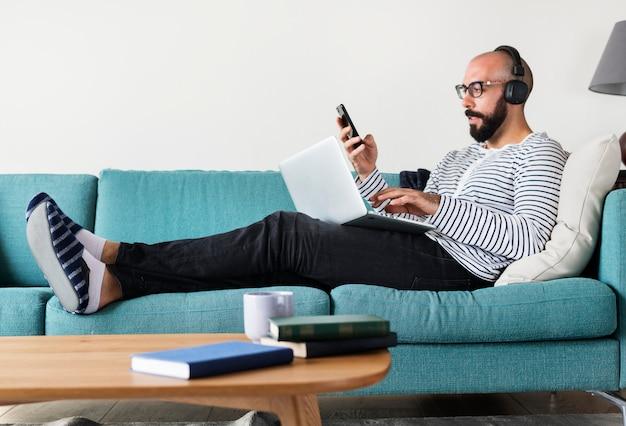 Homem, usando, dispositivo, ligado, sofá