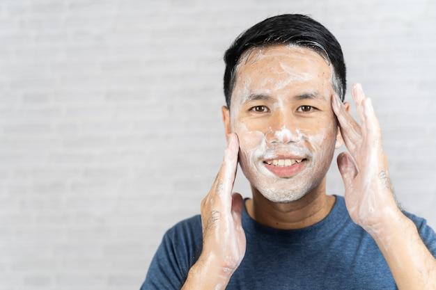 Homem usando espuma lavando o rosto em fundo cinza