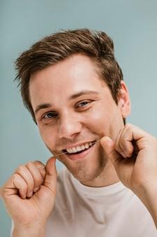 Homem usando fio dental