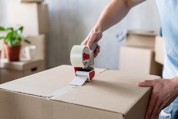 Homem usando fita adesiva na caixa, pronto para sair