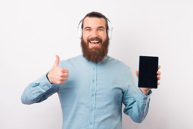 Homem usando fones de ouvido está mostrando a tela para a câmera e o polegar para cima.