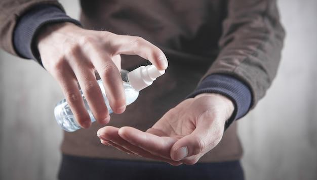 Homem usando gel desinfetante para as mãos.
