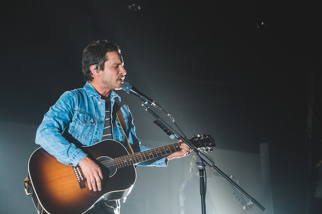 Homem usando guitarra enquanto se apresenta no palco