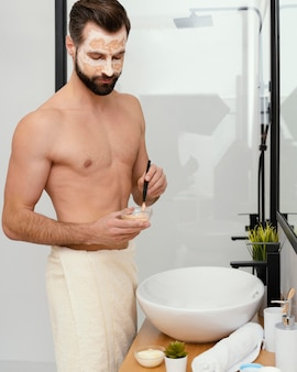 Homem usando ingredientes naturais como máscara facial