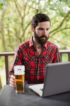 Homem usando laptop com copo de cerveja na mesa
