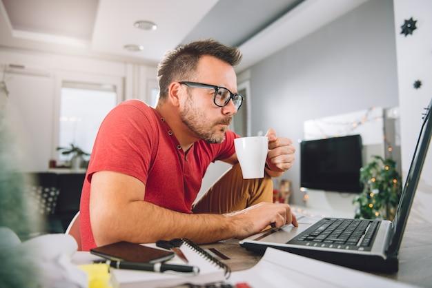 Homem usando laptop e bebendo café