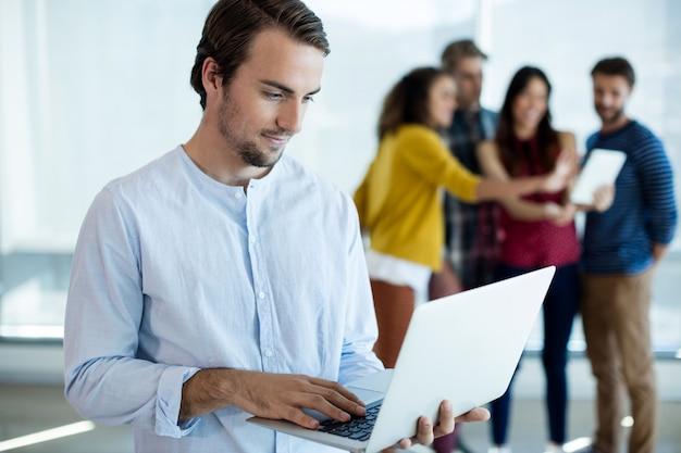 Homem usando laptop enquanto colegas discutem no escritório