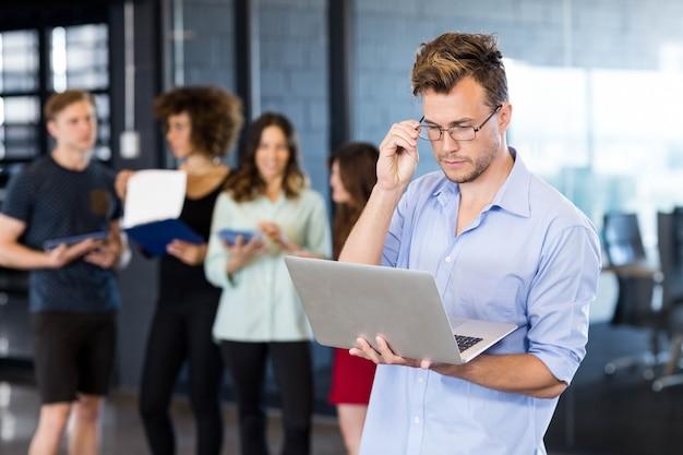 Homem, usando, laptop, enquanto, colegas, estar, atrás de, escritório