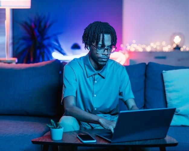 Homem usando laptop enquanto está no sofá em casa Foto gratuita