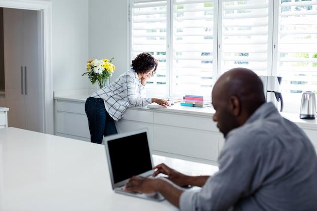 Homem usando laptop enquanto mulher lendo livro no fundo