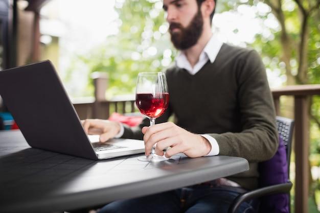 Homem usando laptop enquanto toma um copo de vinho