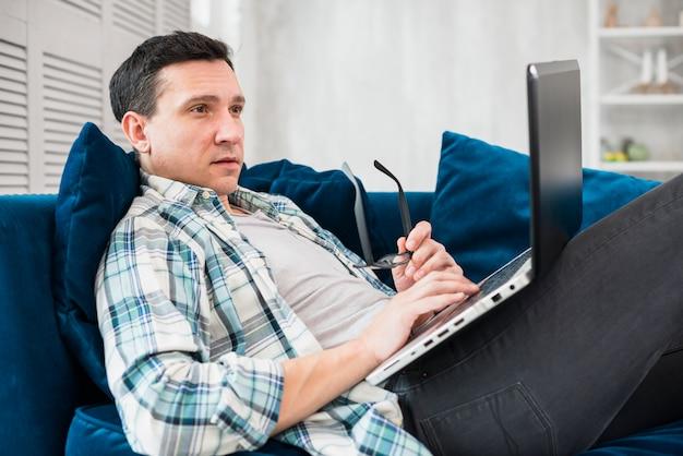 Homem, usando, laptop, ligado, canapé