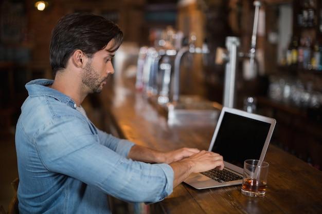 Homem usando laptop no balcão de bar