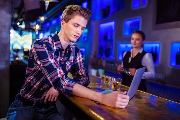 Homem usando laptop no bar balcão com barman trabalhando