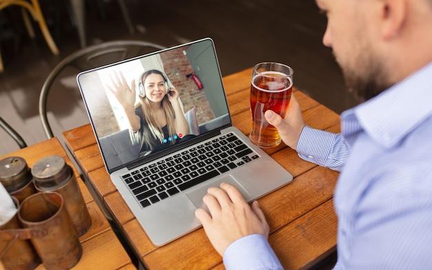 Homem usando laptop para videochamada enquanto bebe cerveja