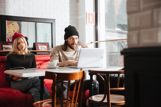 Homem usando laptop perto da namorada no café