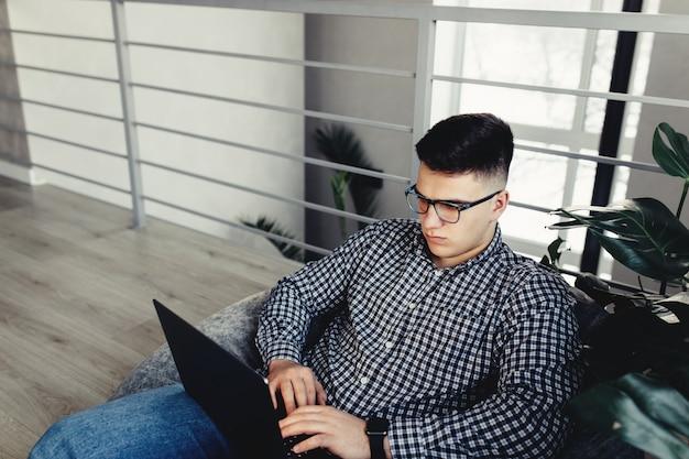 Homem usando laptop, usando óculos, móveis acolchoados. fundo desfocado. foto de alta qualidade
