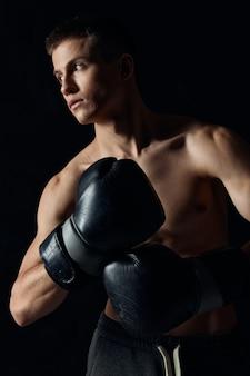 Homem usando luvas de boxe torso nu fundo preto vista recortada modelo fitness fisiculturista