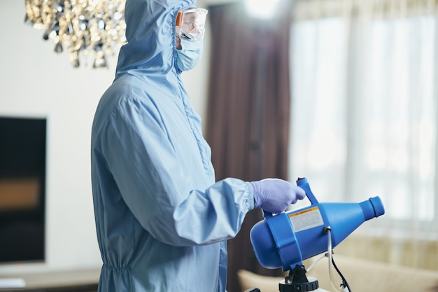 Homem usando luvas de proteção e segurando desinfetante na sala