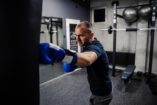 Homem usando luvas e batendo em um saco de boxe preto em uma academia de boxe com um espelho