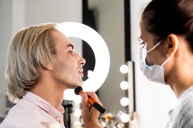 Homem usando maquiagem e vista lateral do salão de beleza