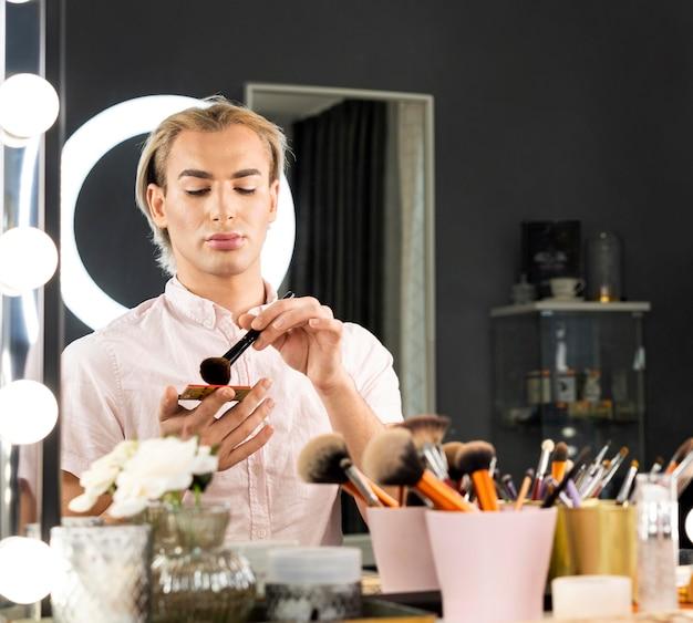 Homem usando maquiagem no espelho
