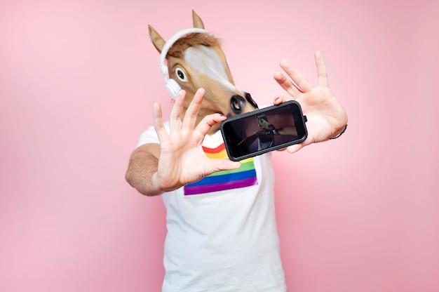 Homem usando máscara de cavalo enquanto tira uma selfie com smartphone