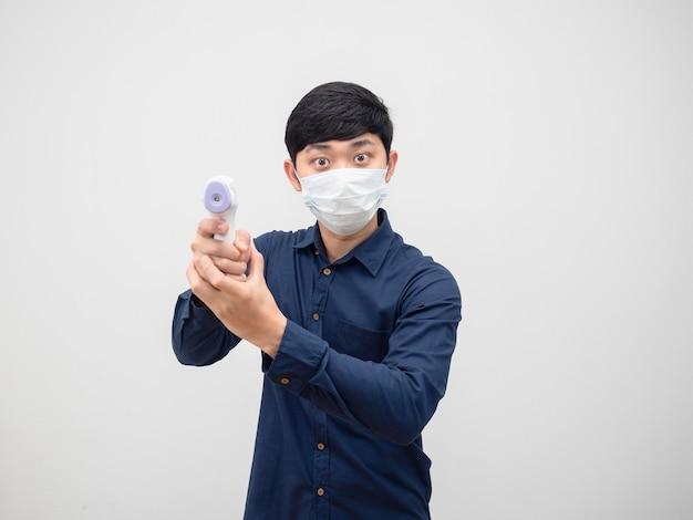 Homem usando máscara de proteção segurando temômetro infravermelho para verificar a temperatura em fundo branco