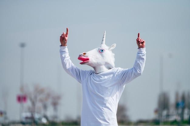 Homem usando máscara de unicórnio fazendo gesto com o dedo apontando para cima